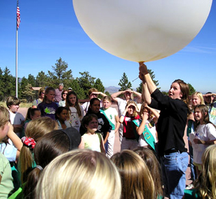 People standing around a woman holding a large white balloon